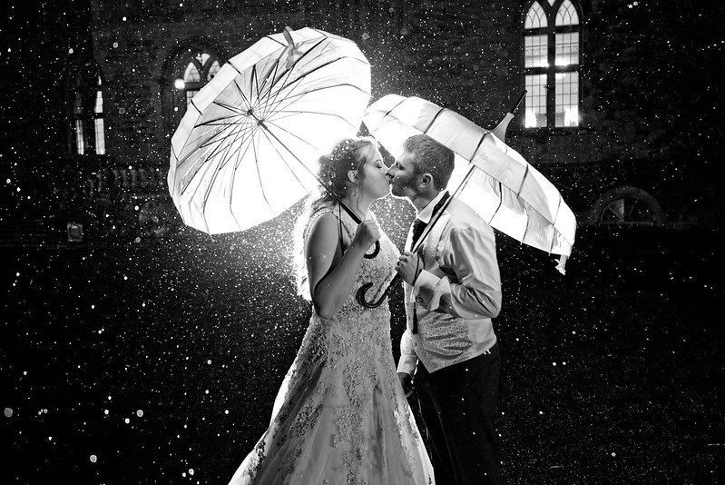 a newly-wed couple, in the dark, holding umbrellas kiss in the rain, with the light reflecting off the raindrops