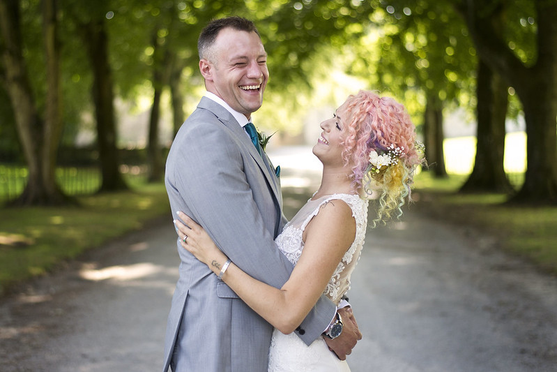 relaxed newly wed embracing couple share a moment of laughter in their professional wedding photographs by Caz Holbrook