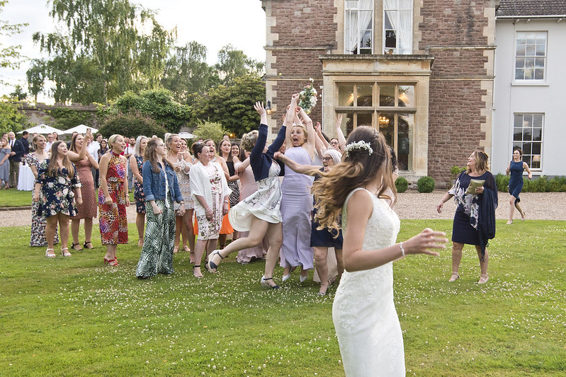 candid photograph of the bouquet toss by Caz Holbrook