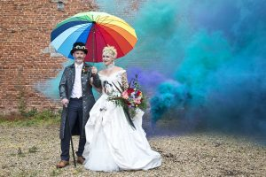 quirky, alternative wedding newly wed couple with a steam punk style under rainbow umbrella with blue smoke in the background