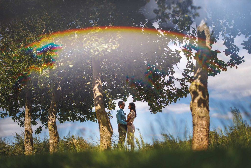 couple embrace under apple trees after their intimate outdoor commitment ceremony in a Herefordshire Orchard by Jennie Hermolle Humanist Wedding Celebrant