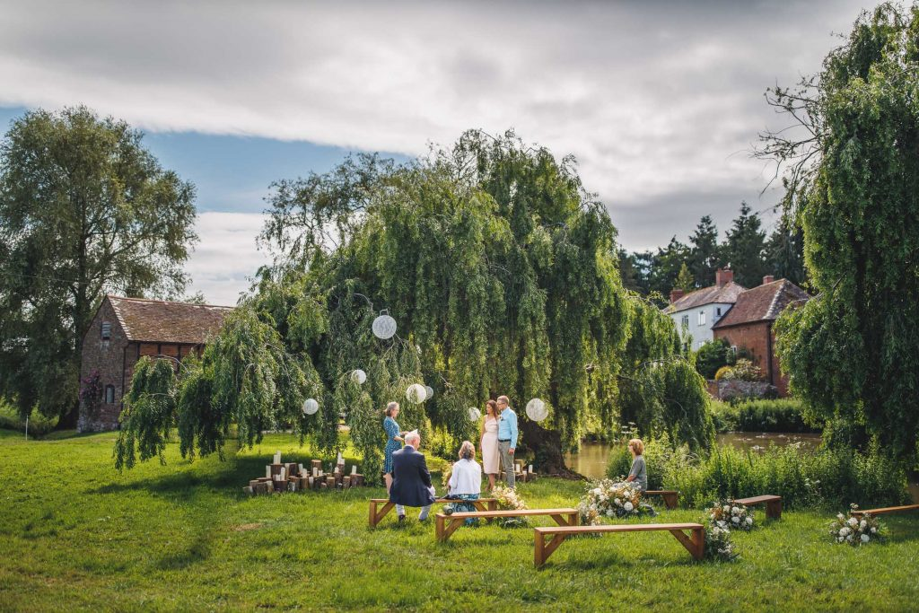 intimate outdoor commitment ceremony socially distanced infrront of a decorated weeping willow at The Orchard and Munsley led by humanist wedding celebrant Jennie Hermolle