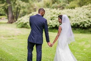 bride and groom walk away together down a grassy path