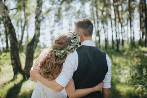 bride embraces groom with her head on his shoulder in a beautiful sunlit woodland wedding ceremony setting for a humanist wedding ceremony