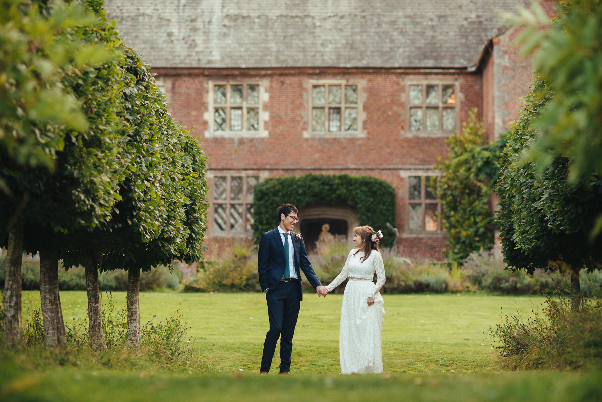 bride and groom stand holding hands in front of Herefordshire country house wedding venue
