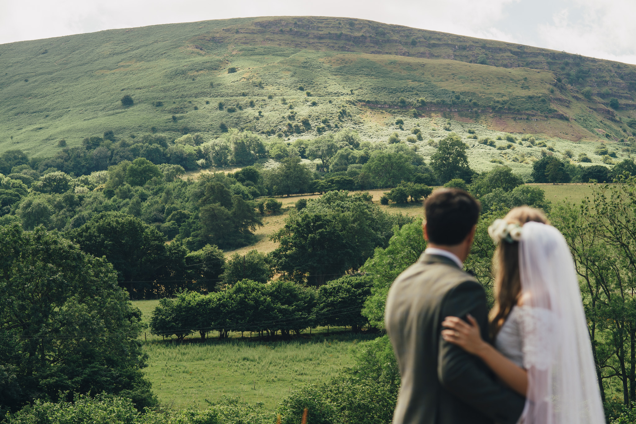 couple stand taking in the view from their black mountain Herefordshire hilltop wedding venue Cat Beardsley